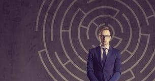 Affärsman med portföljanseende på en labyrintbakgrund B Royaltyfri Fotografi