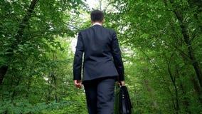 Affärsman med portföljen som går i skogen som tycker om sikt, flykt från stad arkivfoton