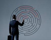 Affärsman med portföljen som står över labyrintbakgrund B royaltyfria bilder