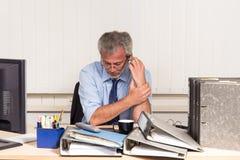 Affärsman med sammanbrott overstressed på hans kontorsskrivbord Royaltyfri Bild