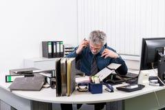 Affärsman med sammanbrott overstressed på hans kontorsskrivbord Arkivbilder