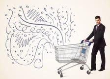 Affärsman med shoppingvagnen Royaltyfri Foto