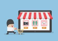 Affärsman med shoppingvagnen framme av online-lagret Royaltyfri Foto