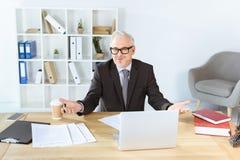 Affärsman med skrivbordsarbete och bärbara datorn Royaltyfri Bild