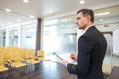 Affärsman med skrivplattaanseende i tom konferenskorridor fotografering för bildbyråer