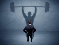 Affärsman med skugga för lyfta för vikt arkivbild