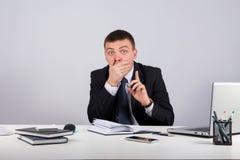 Affärsman med smartphonen som rymmer hans finger främst av hans mun och gör tystnadgest shh arkivbilder