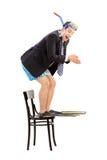 Affärsman med snorkeln som hoppar av en stol royaltyfria foton