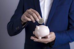 Affärsman med spargrisen och bitcoin royaltyfri bild