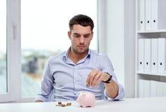 Affärsman med spargrisen och mynt på kontoret Arkivfoto