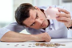 Affärsman med spargrisen och mynt på kontoret Arkivbild