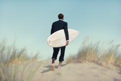 Affärsman med surfingbrädan som går till stranden Arkivfoto