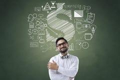 Affärsman med symboler på den svart tavlan Arkivfoton