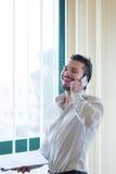 Affärsman med telefonen som är främst av fönstret royaltyfria bilder