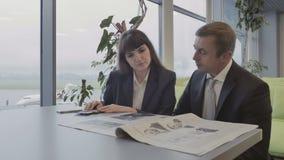 Affärsman med tidningen och väntningar för kvinna den läs- logiet på nivån arkivfilmer