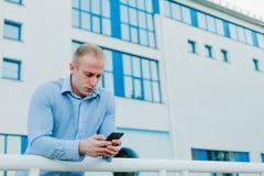 Affärsman nära en byggnad som grubblar ett affärsplan Fotografering för Bildbyråer