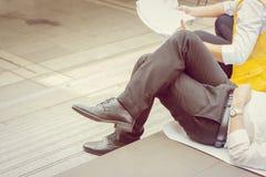 Affärsman och affär som iscensätter koppla av att ligga och att sitta på golvet royaltyfria foton