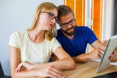 Affärsman och affärskvinna som analyserar diagram på minnestavlaPC av Arkivfoton