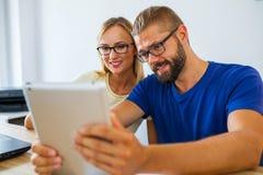 Affärsman och affärskvinna som analyserar diagram på minnestavlaPC av Fotografering för Bildbyråer