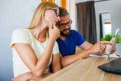 Affärsman och affärskvinna som analyserar diagram på minnestavlaPC av Royaltyfri Fotografi