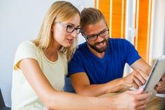 Affärsman och affärskvinna som analyserar diagram på minnestavlaPC av Royaltyfri Bild