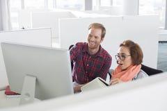Affärsman och affärskvinna som använder datoren i idérikt kontor Royaltyfri Fotografi