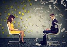 Affärsman och affärskvinna som arbetar på bärbar datordator en under pengarregn annat under ljusa kulor för ljusa idéer Royaltyfria Bilder