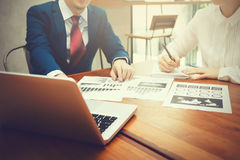Affärsman och affärskvinna som diskuterar och pekar på finansiella och strategidokument med bärbara datorn under affärsmöte Arkivfoton
