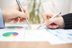 Affärsman och affärskvinna som granskar analysen av kompet Arkivfoto