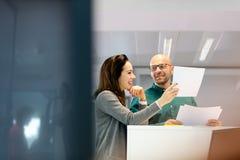 Affärsman och affärskvinna som i regeringsställning diskuterar över dokument Arkivfoto
