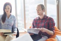 Affärsman och affärskvinna som i regeringsställning fungerar arkivfoton