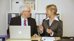 Affärsman och affärskvinna som i regeringsställning talar arkivfilmer