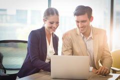 Affärsman och affärskvinna som påverkar varandra genom att använda bärbara datorn arkivbilder