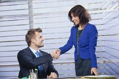 Affärsman och affärskvinna som skakar händer royaltyfri bild