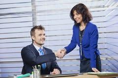 Affärsman och affärskvinna som skakar händer royaltyfri fotografi