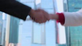 Affärsman och affärskvinna som skakar händer, fulländande övre ett möte arkivfilmer