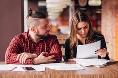 Affärsman och affärskvinna som studerar dokument i ett kafé royaltyfri fotografi