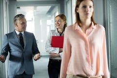 Affärsman och affärskvinna som talar, medan gå i korridor med den kvinnliga kollegan i förgrund på kontoret royaltyfri fotografi