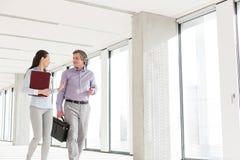 Affärsman och affärskvinna som talar, medan gå i nytt kontor arkivbilder
