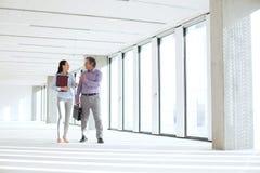 Affärsman och affärskvinna som talar, medan gå i tomt kontor royaltyfri fotografi