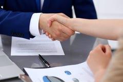 Affärsman och affärskvinna som till varandra skakar händer ovanför undertecknat avtal Arkivfoton