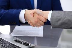 Affärsman och affärskvinna som till varandra skakar händer ovanför undertecknat avtal Arkivbilder
