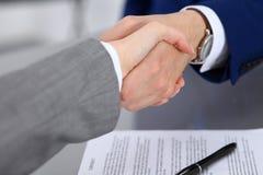 Affärsman och affärskvinna som till varandra skakar händer ovanför undertecknat avtal Royaltyfria Bilder