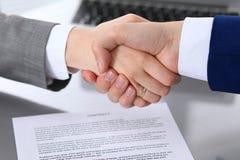 Affärsman och affärskvinna som till varandra skakar händer ovanför undertecknat avtal Royaltyfri Bild
