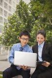 Affärsman och affärskvinna som tillsammans utomhus arbetar på bärbara datorn Arkivfoto