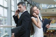 Affärsman och affärskvinna tillbaka som ska dras tillbaka på mobiltelefoner Fotografering för Bildbyråer