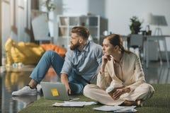 Affärsman- och affärskvinnasammanträde på golv och användabärbara datorn Arkivbild
