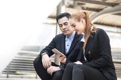 Affärsman och affärskvinnor som läser meddelandet i smart telefon arkivfoto