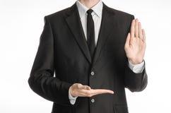 Affärsman och gestämne: en man i en svart dräkt med ett band som visar på ett stopptecken med hans vänstersidahand och håll hans  Royaltyfri Fotografi