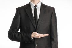 Affärsman och gestämne: en man i en svart dräkt och band som rymmer hans hand främst av honom, isolerade på en vit bakgrund i st Royaltyfri Bild